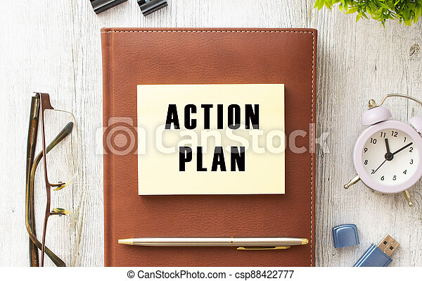 Notepad with the text ACTION PLAN on a wooden table. Brown diary and pen. - csp88422777