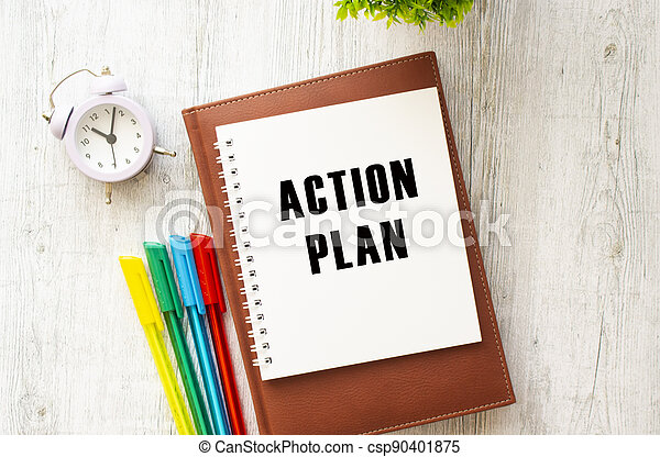 Notepad with the text ACTION PLAN on a wooden table. Brown diary and pens. - csp90401875