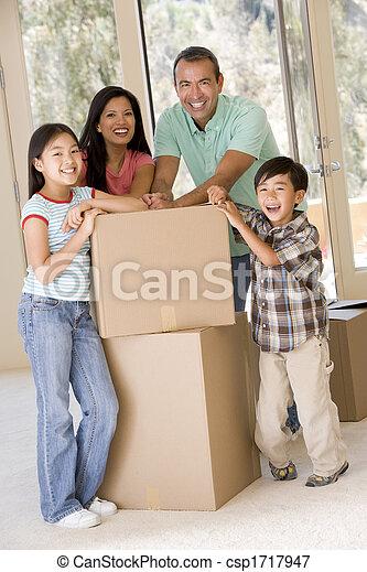 Familia con cajas en un nuevo hogar sonriendo - csp1717947