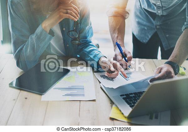 Gerentes de ventas trabajando en un estudio moderno. Una mujer que muestra un informe de mercado informa de tabletas digitales. El departamento de mercado planea una nueva estrategia. - csp37182086