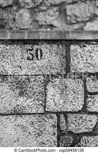 Number 50, black and white, stone wall, upper left - csp59456126