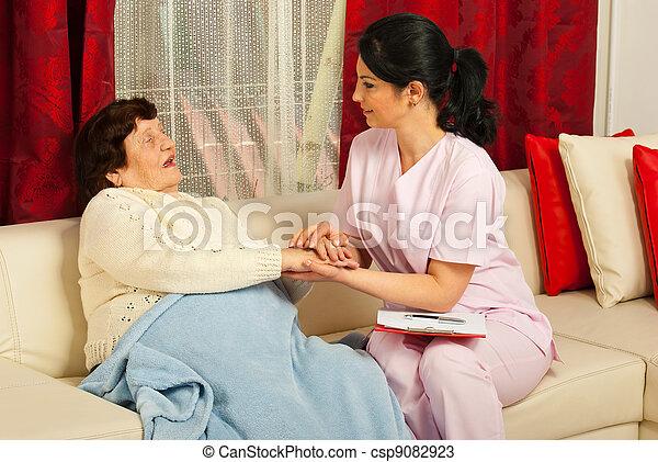 Nurse comforting sick elderly woman - csp9082923