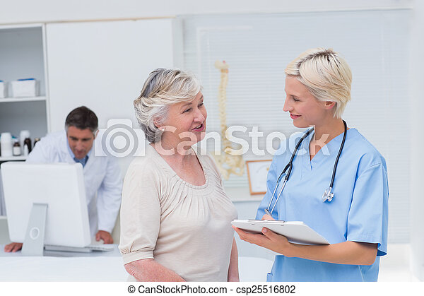 Nurse discussing with patient while doctor using computer - csp25516802