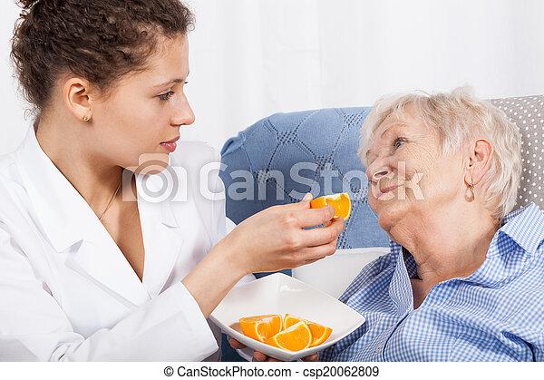 Nurse feeding an elderly woman - csp20062809