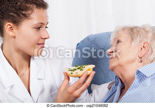 Nurse feeding elderly woman - csp21049082