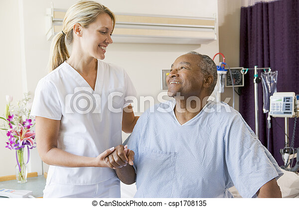 Nurse Helping Patient Sit Up In Bed - csp1708135