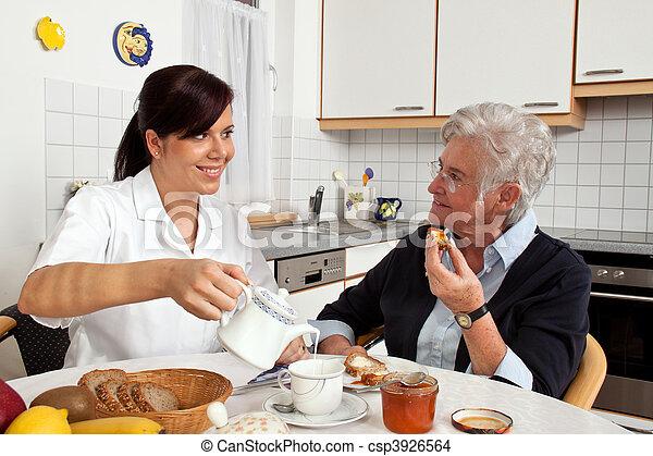 Nurse helping senior citizen at breakfast - csp3926564