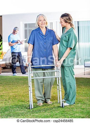 Nurse Helping Senior Woman To Use Walking Frame In Lawn - csp24456485