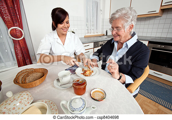 nurse helps elderly woman at breakfast - csp8404698