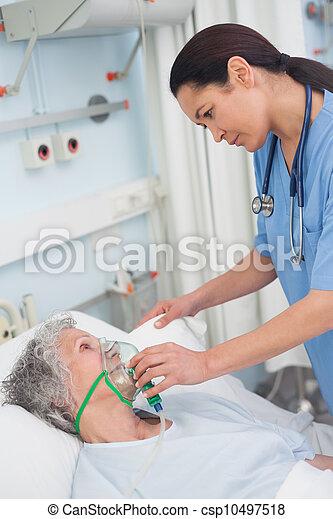 Nurse putting oxygen mask on a patient - csp10497518