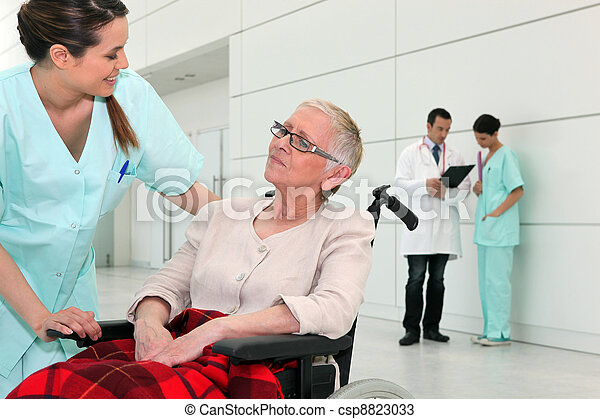 Nurse talking to an elderly woman in a wheelchair - csp8823033