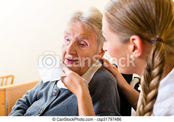 Nurse wiping mouth of senior woman in nursing home - csp31797486