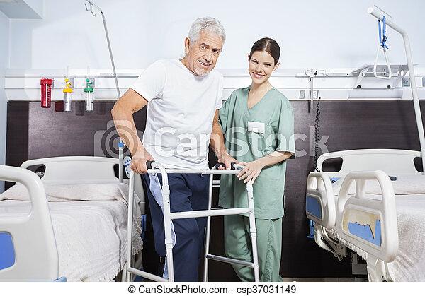 Nurse With Senior Man Using Walker In Rehab Center - csp37031149