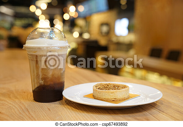nut caramel moon cake with ice latte coffee beside, on the wood table. - csp67493892