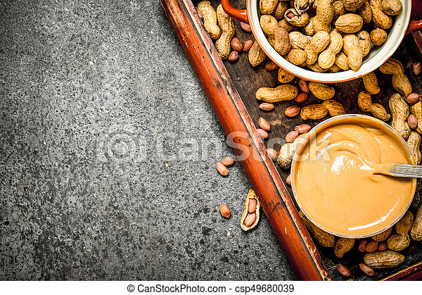 Nuts and peanut butter in a bowl. - csp49680039
