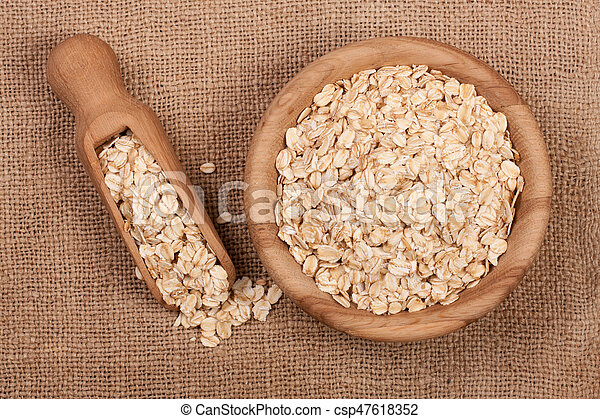 Oat flakes in a wooden bowl with a scoop on sackcloth - csp47618352