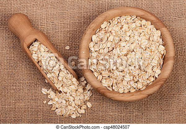 Oat flakes in a wooden bowl with a scoop on sackcloth - csp48024507