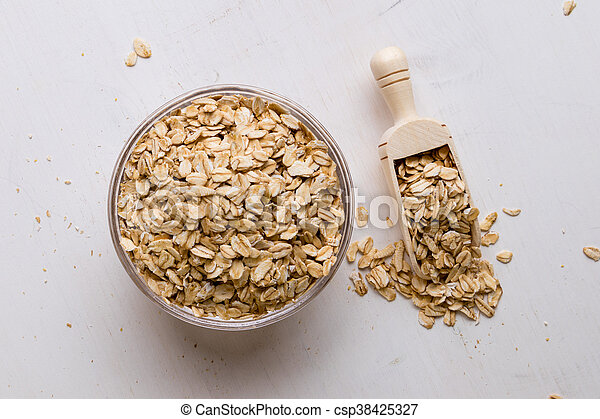 oat flakes in bowl and scoop - csp38425327