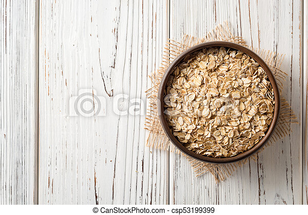 Oat flakes in ceramic bowl on white wooden table - csp53199399