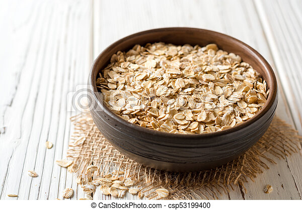 Oat flakes in ceramic bowl on white wooden table - csp53199400