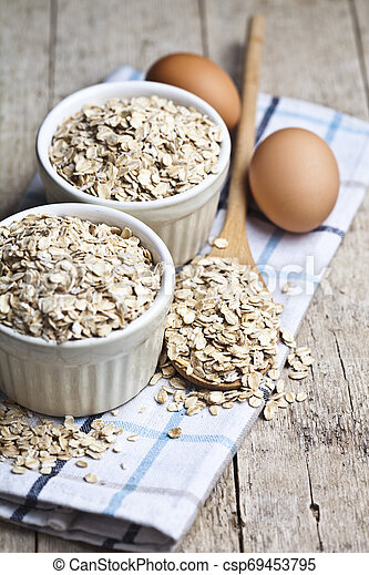 Oat flakes in ceramic bowls and wooden spoon and fresh chicken eggs on rustic wooden table background. - csp69453795