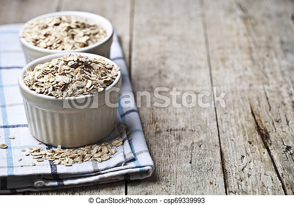 Oat flakes in ceramic bowls on linen napkin, golden wheat ears on rustic wooden background. - csp69339993