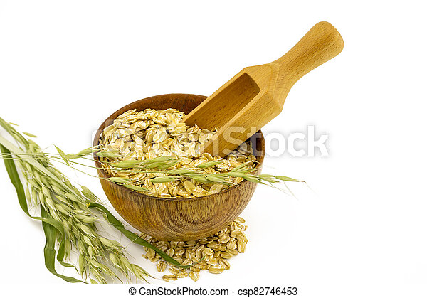 Oat flakes in the bowl, wooden scoop branch - csp82746453