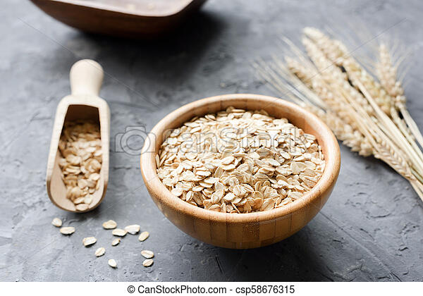 Oat flakes in wooden bowl and golden wheat ears - csp58676315
