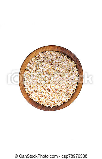 Oat-flakes in wooden bowl. Isolated. Top view. - csp78976338