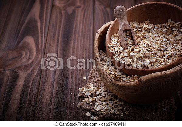 Oat flakes in wooden bowl - csp37469411