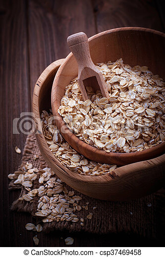 Oat flakes in wooden bowl - csp37469458