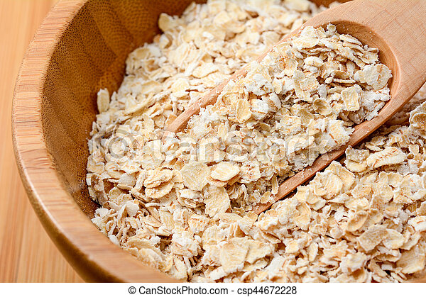 oat flakes in wooden bowl - csp44672228