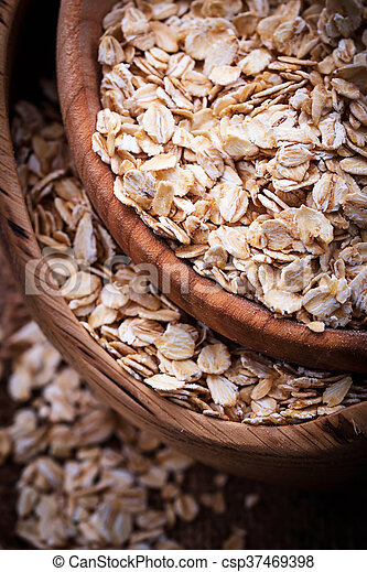 Oat flakes in wooden bowl - csp37469398