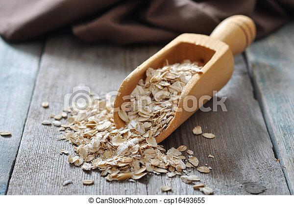 oat flakes in wooden scoop - csp16493655