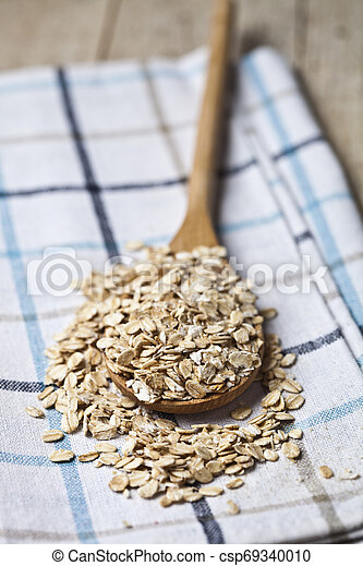 Oat flakes in wooden spoon on linen napkin, golden wheat ears on rustic wooden background. - csp69340010
