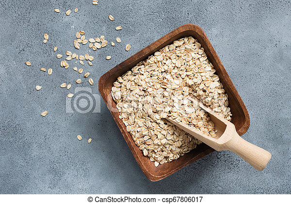 Oat flakes, rolled oats in wooden bowl with scoop - csp67806017