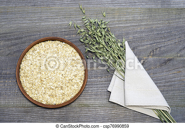 Oatmeal flakesl in a ceramic bowl on a rustic wooden table background and green ears of oats in a white linen napkin. - csp76990859