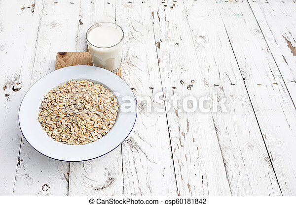 Oatmeal, rolled oats on white wooden background wilt glass of milk. Porridge oats flakes - csp60181842