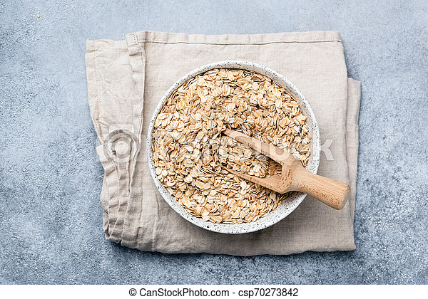 Oats or oat flakes in bowl on linen textile - csp70273842