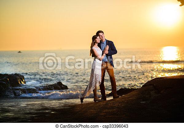 Una pareja enamorada viendo una puesta de sol en la playa - csp33396043
