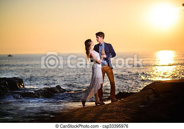 Una pareja enamorada viendo una puesta de sol en la playa - csp33395976