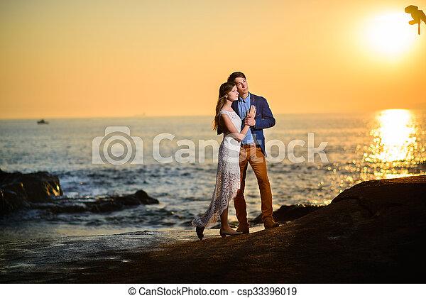 Una pareja enamorada viendo una puesta de sol en la playa - csp33396019