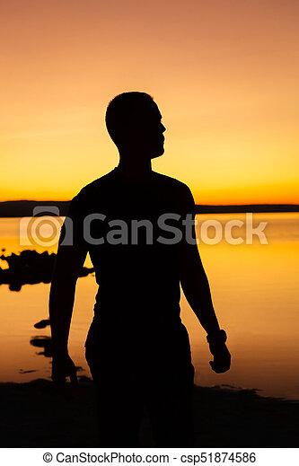 La silueta de un hombre al atardecer - csp51874586