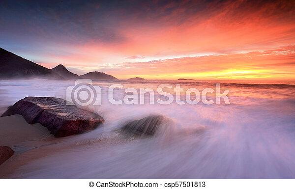 Ocean sunrise as large waves wash onto the beach - csp57501813