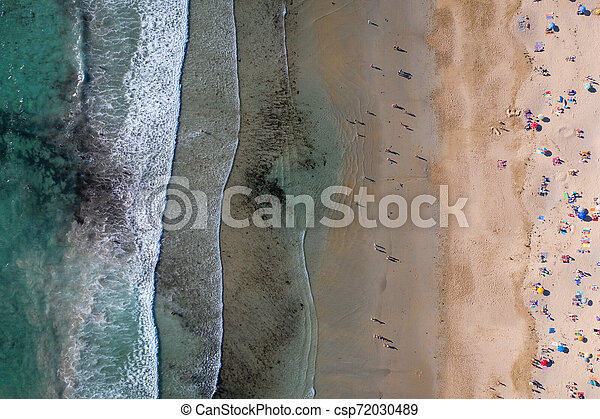 ocean waves, sandy beach with people bathing in the water, view from drone, Lanzada beach, Galicia, Spain - csp72030489