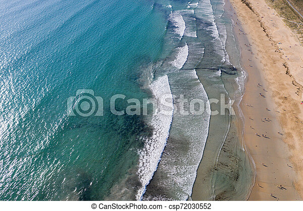 ocean waves, sandy beach with people bathing in the water, view from drone, Lanzada beach, Galicia, Spain - csp72030552