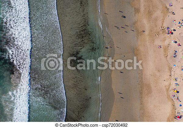 ocean waves, sandy beach with people bathing in the water, view from drone, Lanzada beach, Galicia, Spain - csp72030492