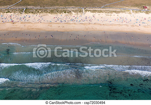 ocean waves, sandy beach with people bathing in the water, view from drone, Lanzada beach, Galicia, Spain - csp72030494