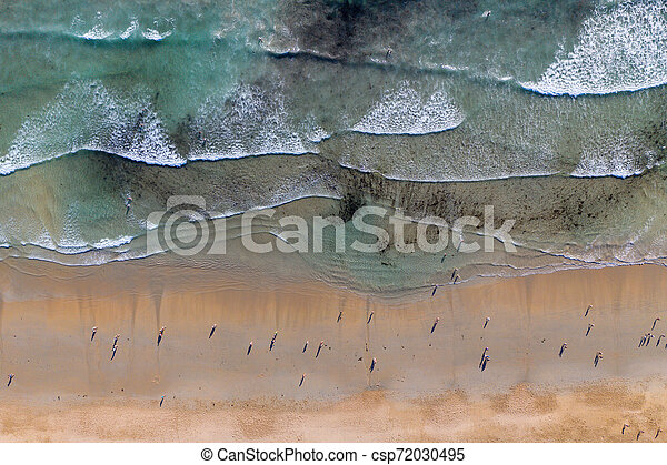 ocean waves, sandy beach with people bathing in the water, view from drone, Lanzada beach, Galicia, Spain - csp72030495