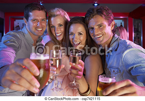 Un grupo de jóvenes divirtiéndose en un bar ocupado - csp7421115